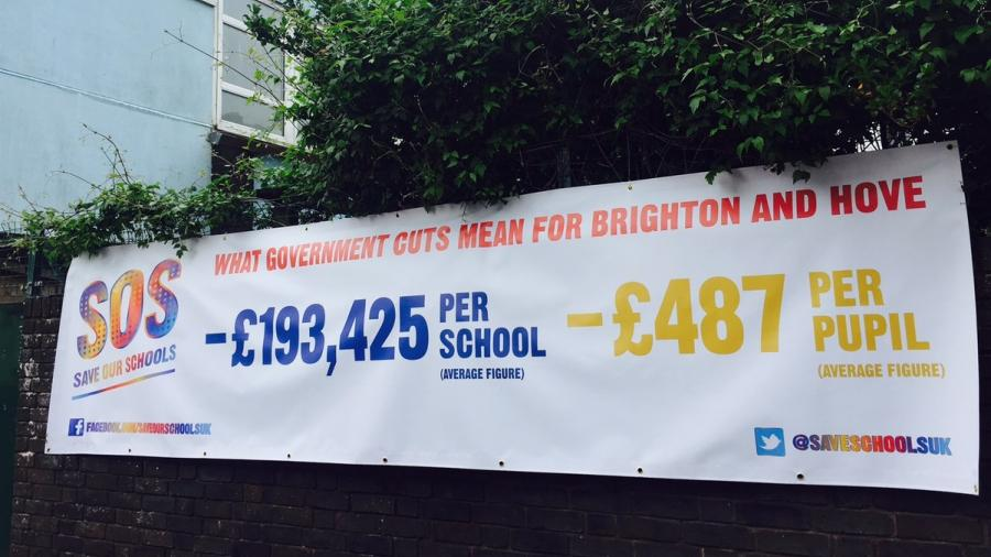 A picture of a banner on a school wall showing figures for funding cuts